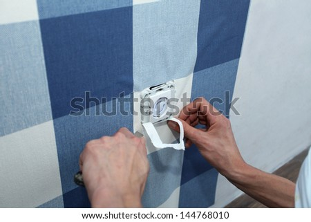 details decorator with scalpel hanging wallpaper over wall socket - stock photo