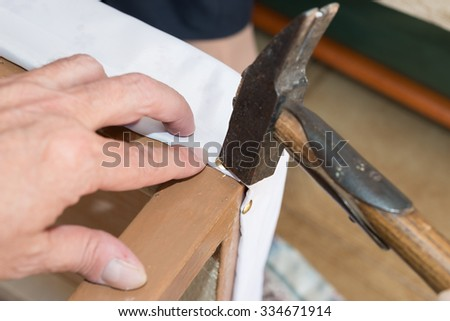 Details elderly person  renewal of the upholstery of a chair - stock photo