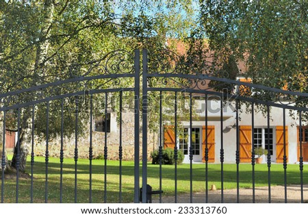 details of a black wrought iron gate in front of house - stock photo