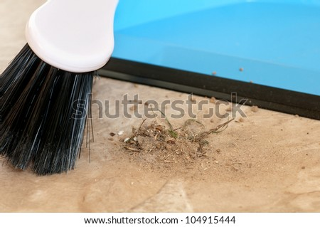 Details of a broom sweeping dirt into a dust pan in either a house or a business. - stock photo