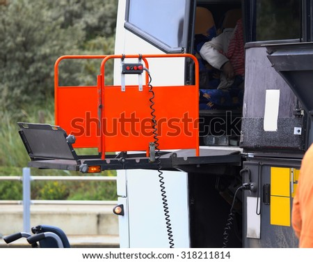 details of a bus using a chair lift for wheelchair - stock photo