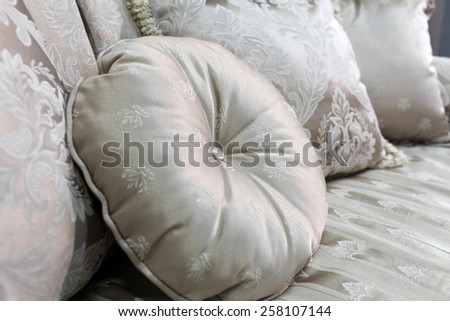 Details of a colorful round cushion on a bed - stock photo