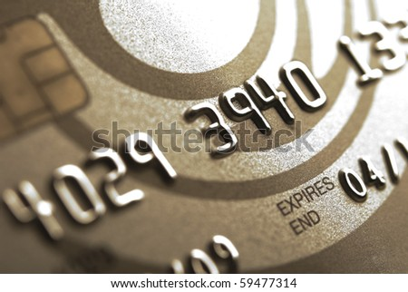 Details of a gold credit card with chip and some numbers, shallow DOF - stock photo