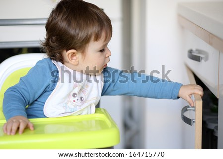 Details of a little boy who is trying to open a drawer in kitchen.
