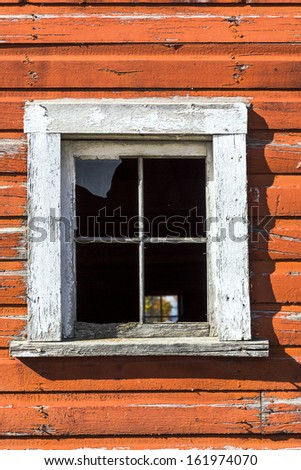 Details of a window on an old red barn - stock photo