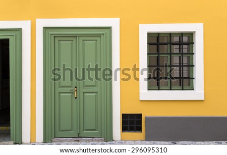 Details of a yellow house with green door and window