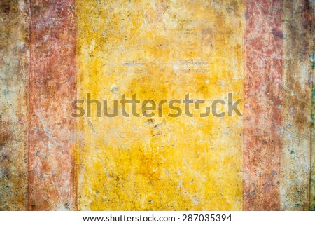 Details of an ancient roman plastered colorfully painted surface with scratches and spots, useful for background, grunge or vintage style. Old town of Ostia, Rome, Italy.