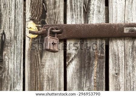 Details of an old locked wooden door with padlock - stock photo