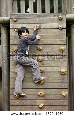 Details of an outdoors climbing girl on a climbing wall for kid.