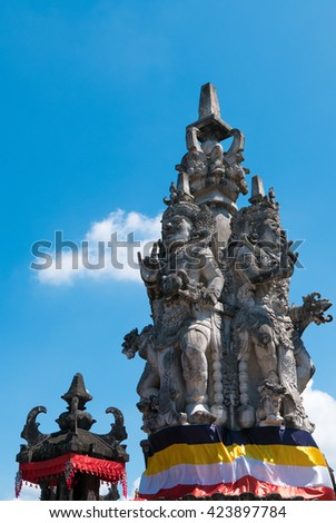 Details of Balinese temple with Hinduism figures in Bali. Clear blue sky in Indonesia - stock photo