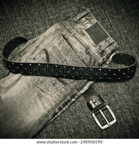 Details of clothes: fashion jeans, a leather belt with a buckle. Black and white photo in retro style - stock photo