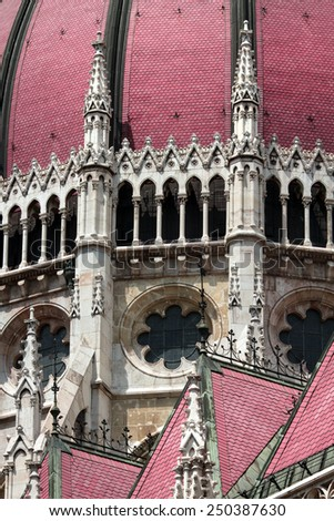 Details of gothic architecture of the main building of the Hungarian Parliament in Budapest. Towers, Crabbe and bright red-purple roof - stock photo