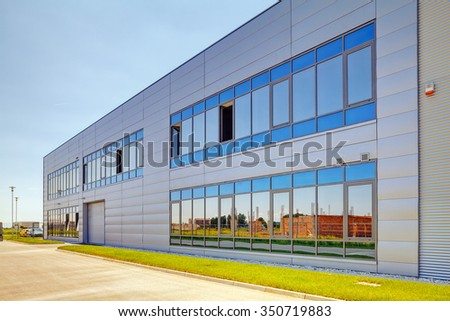 Details of gray facade made of aluminum panels  with doors and windows on industrial building