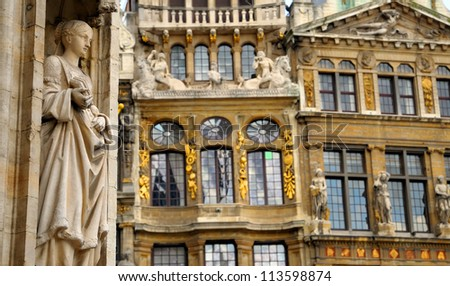 Details of medieval architecture of building on Grand Place in Brussels with realistic gothic statue - stock photo