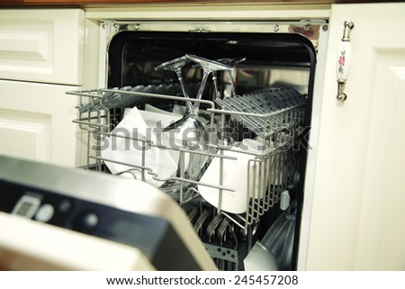 details of Open dishwasher with clean utensils - stock photo