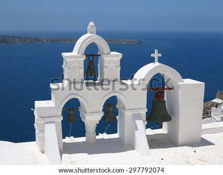 details of Santorini island Greece - beautiful typical church with white belfry and blue sea - stock photo