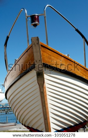Details of the front part of a prow of a wooden yacht boat  with clear blue sky background - stock photo