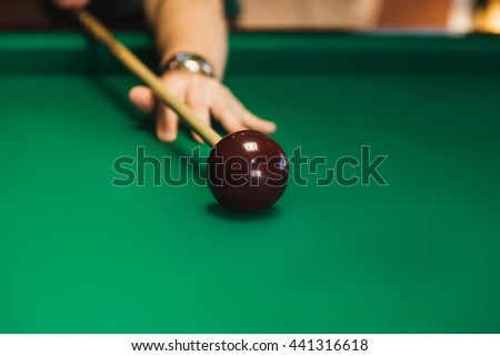 Details of the game of billiards. Red ball in the center of the frame. Player aiming cue in a billiard ball. - stock photo
