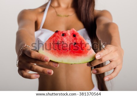 Details of the hands of a young woman with a slice of watermelon