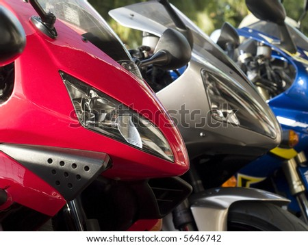 Details of three motorbikes. Shallow depth of field with the first bike in focus.