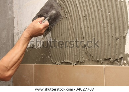 details of trowel spreading mortar for ceramic tile - stock photo