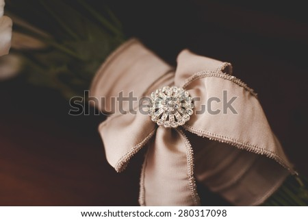 Details of wedding bouquet: bow with a brooch - stock photo