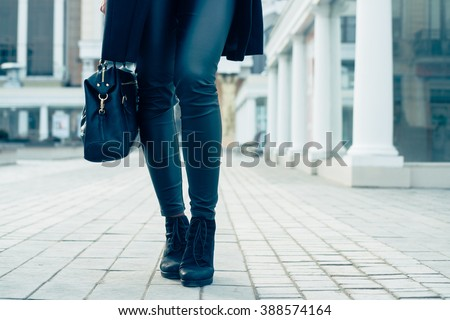 Details of women's clothing. Closeup of female legs in black pants and boots. Woman walking in the city, low-angle shooting, cold toning. - stock photo