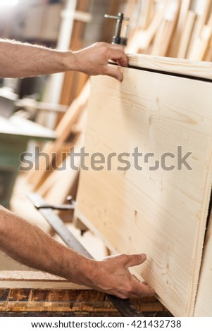 details of woodworker hands with wooden board - stock photo