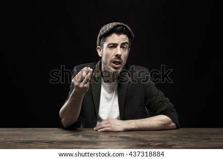 Detained young man sitting at table. Studio shot. - stock photo