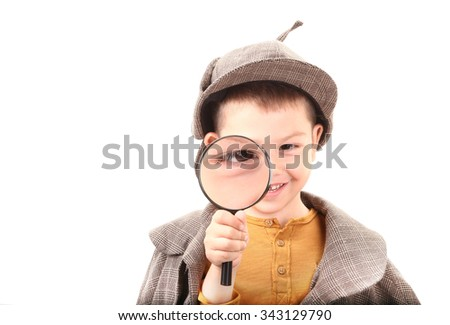 Detective boy is looking through magnifying glass