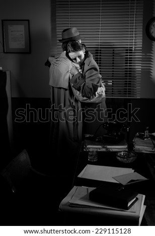 Detective consoling and hugging a young woman in his office, film noir scene.