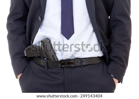 detective, policeman or bodyguard with gun in pants isolated on white background - stock photo