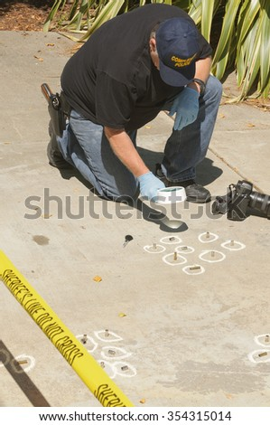 Detective studying a crimes scene taking photographs  - stock photo