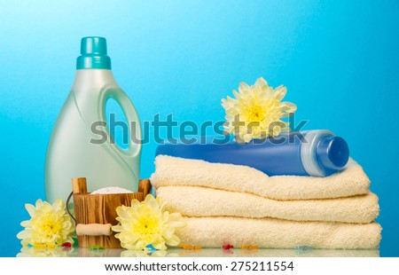Detergent in bottles and towels isolated on blue background - stock photo