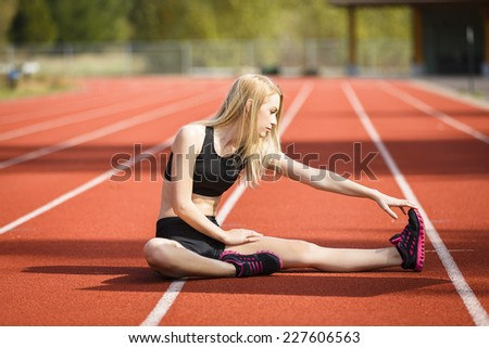 Determine young blond athlete warming up and stretching her legs