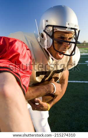 Determined American football player running with ball during competitive game, opposing player attempting tackle, close-up - stock photo