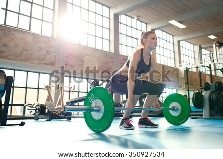 Determined and strong fitness woman training with heavy weights in fitness club. Caucasian female athlete doing weight lifting exercise in gym. - stock photo