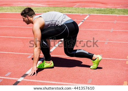 Determined athlete ready to run on running track