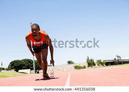 Determined athlete running on the racing track on a sunny day - stock photo