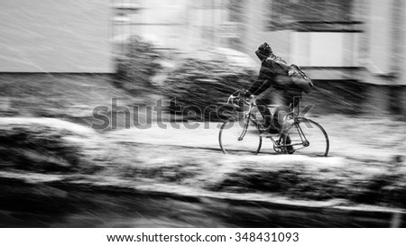 Determined bicyclist pedals through snowstorm in the street
