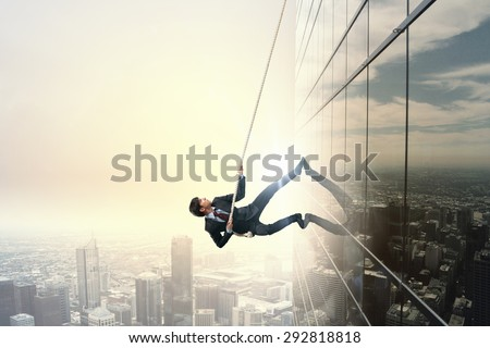 Determined businessman climbing building with help of rope - stock photo