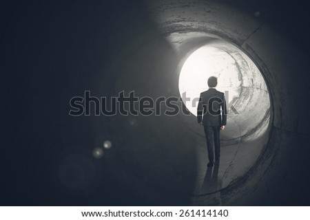 Determined businessman gets out of the tunnel - stock photo