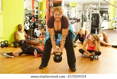 Determined fat woman doing fitness workout in gym, all the others exhausted. - stock photo