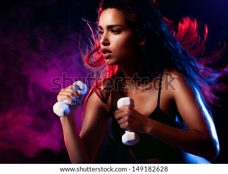 Determined fit sexy woman working out with dumbells on blue and violet smoky wave background - stock photo