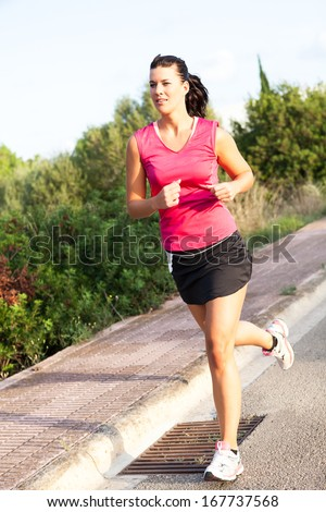 Determined fit young Caucasian woman practicing jogging in the park, in a warm summer day - stock photo