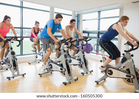 Determined five people working out on exercise bikes in a gym - stock photo