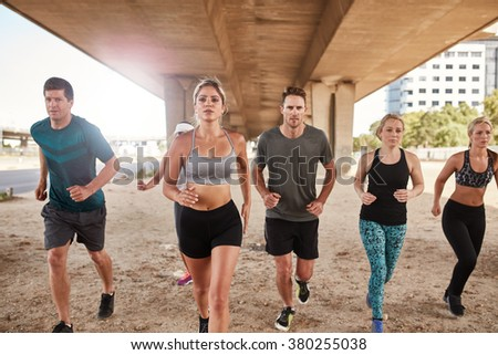 Determined group of athletes running. Runners in sportswear training together in the city. - stock photo