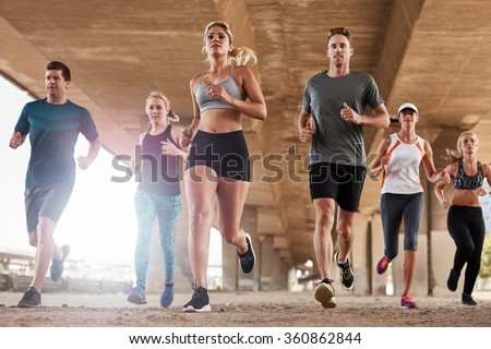 Determined  group of young people running together in city. Low angle shot of running club members training together in morning under a bridge. - stock photo