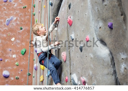determined little boy enjoying rock climbing at indoor climbing gym, healthy and active lifestyle concept