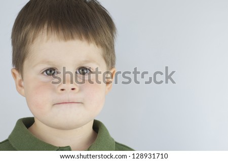 Determined little boy, with lips pursed like he is ready to do whatever,set off to the left of the frame.